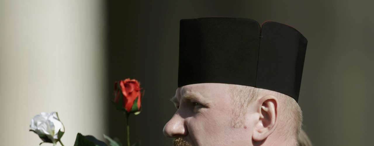 Monge segura rosas enquanto acompanha a última audiência do Papa