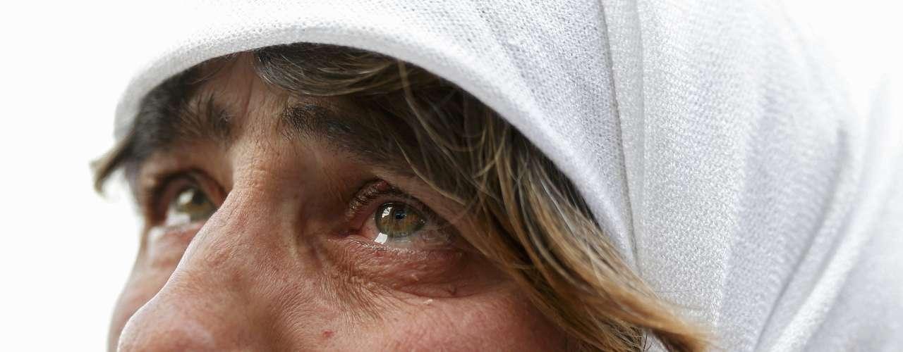 Mulher chora enquanto acompanha a saída do Papa em telão montado na Cidade do Vaticano
