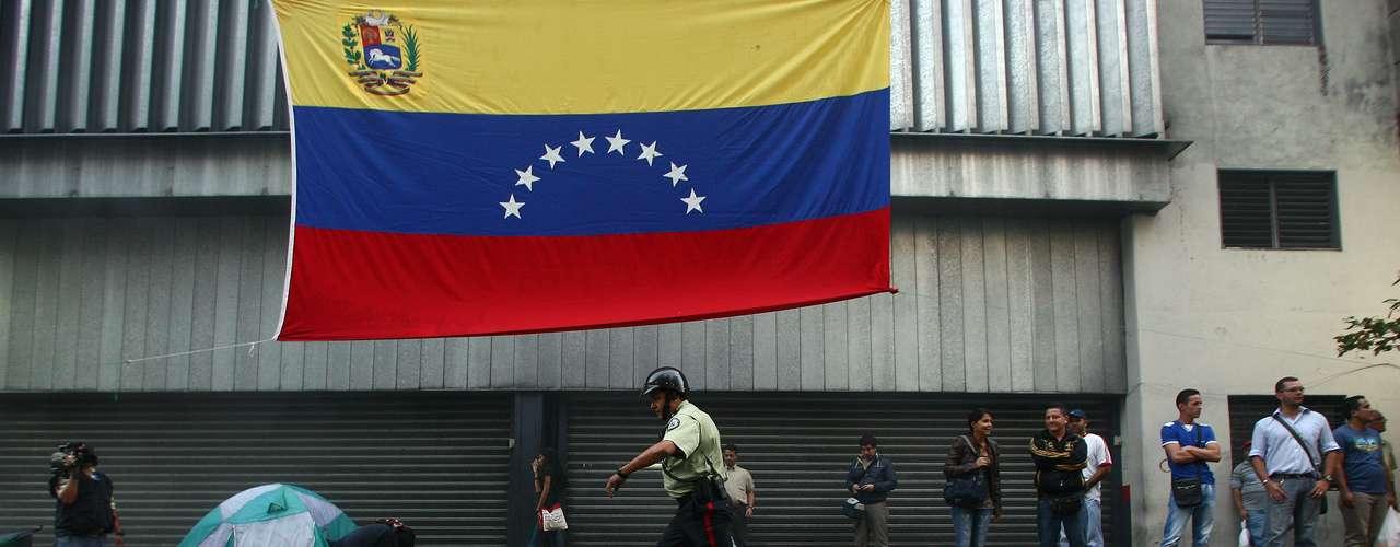 5 de março -Policial caminha em volta dos pertences dos estudantes que se acorrentaram exigindo informações sobre estado de saúde de Chávez