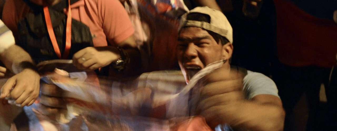 5 de março -Venezuelano balança um retrato de Chávez em frente ao Hospital Militar em Caracas