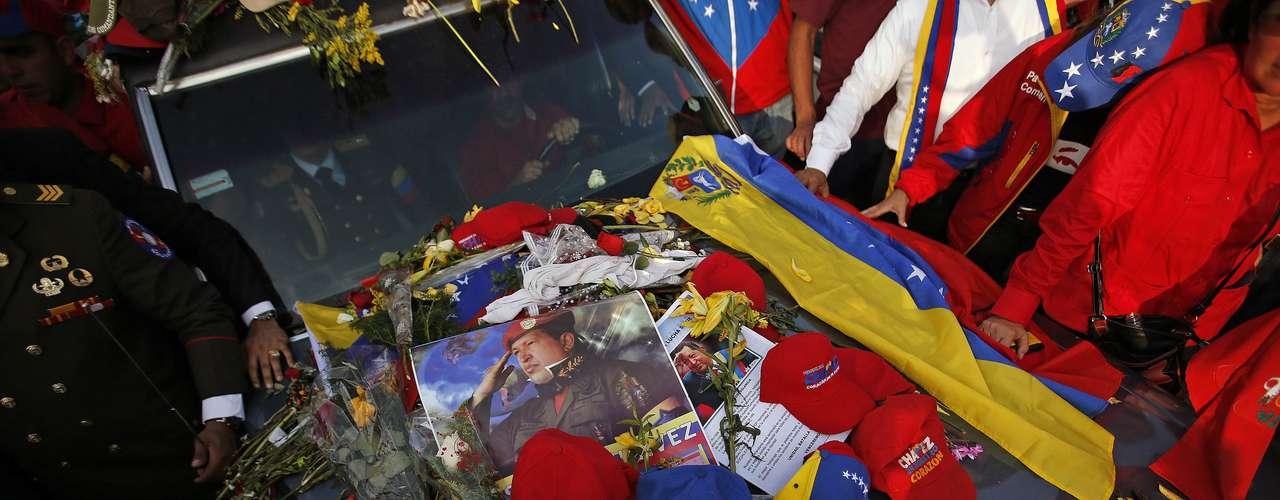 6 de março -Bonés, flores e cartazes são deixados por apoiadores no veículo que transportava o caixão de Chávez do hospital até a Academia Militar