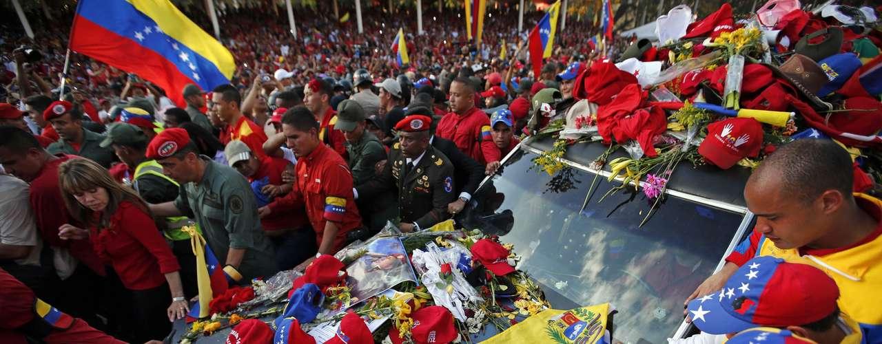 6 de março - Bonés, flores e cartazes são deixados por apoiadores no veículo que transportava o caixão de Chávez do hospital até a Academia Militar