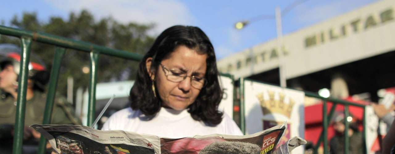6 de março - Venezuelanos leem jornal com a notícia da morte do presidente do país