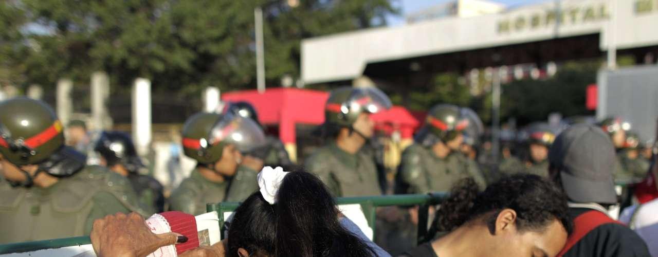 6 de março - Milhares de apoiadores de Chávez permanecem em frente ao Hospital Militar de Caracas, onde Chávez estava internado havia duas semanas. Venezuelanos homenageiam líder com aplausos, gritos ou cantando o hino nacional