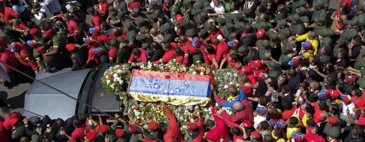 6 de março -Centenas de pessoas acompanham cortejo fúnebre do corpo de Hugo Chávez em uma rua de Caracas, na Venezuela. O primeiro dia após o anúncio de sua morte foi marcado por tristeza e homenagens em todo o país