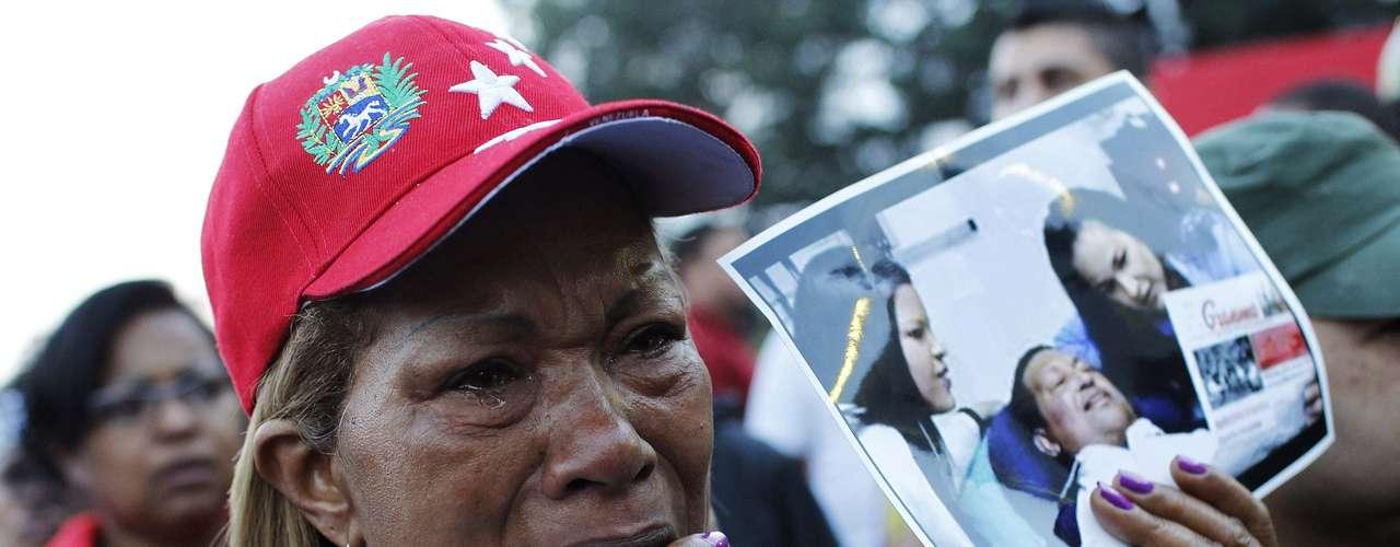 6 de março -Em luto pela morte do líder da Venezuela, mulher chora enquanto segura foto de Chávez no hospital: uma de suas últimas imagens divulgadas