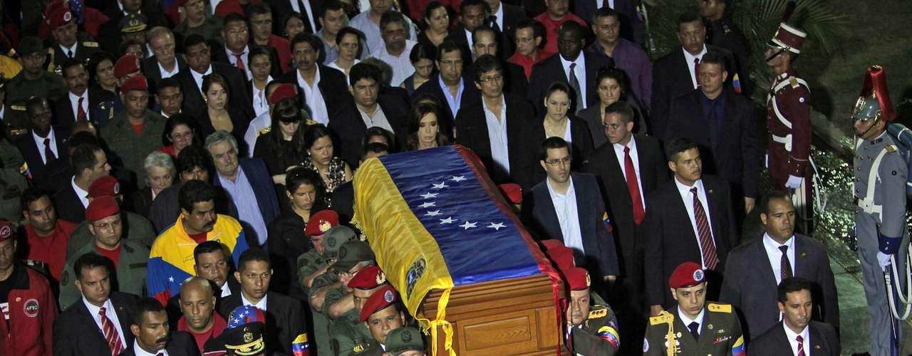 6 de março - O corpo de Chávez é transportado até a Academia Militar de Caracas por oficiais, seguidos por uma multidão