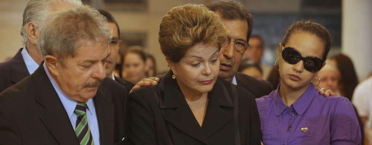 7 de março -Acompanhados da filha de Chávez Rosa Virginia (esq.), o ex-presidente Lula e a presidente Dilma Rousseff se emocionam durante o velório do venezuelano
