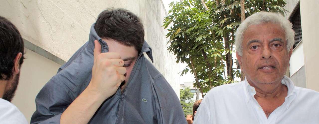 10 de março - O motorista Alex Siwek, que atropelou o ciclista, esconde o rosto ao chegar ao 78º DP com o advogado para prestar depoimento
