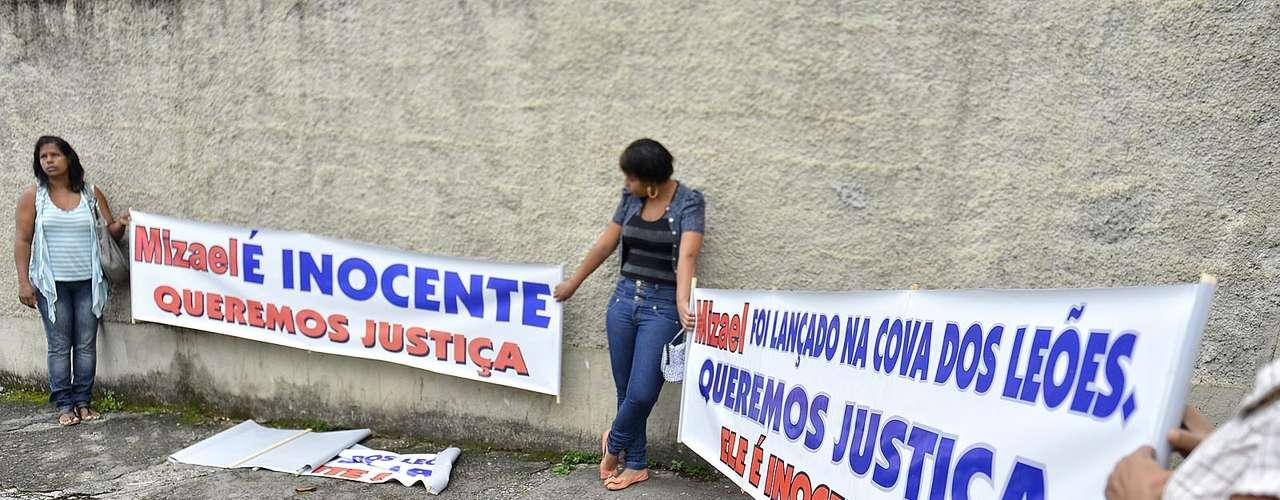 11 de março Manifestantes seguram faixas alegando que o réu é inocente