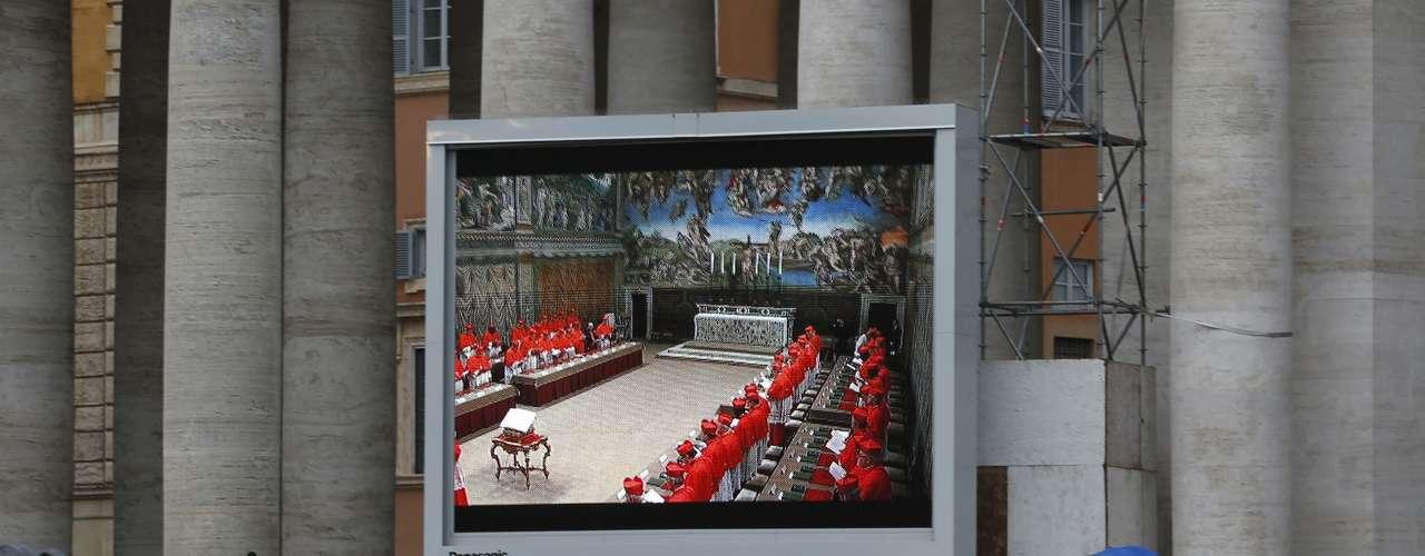 12 de março - Multidão lota a Praça São Pedro para assistir por um telão à missa na Capela Sistina que antecede o conclave