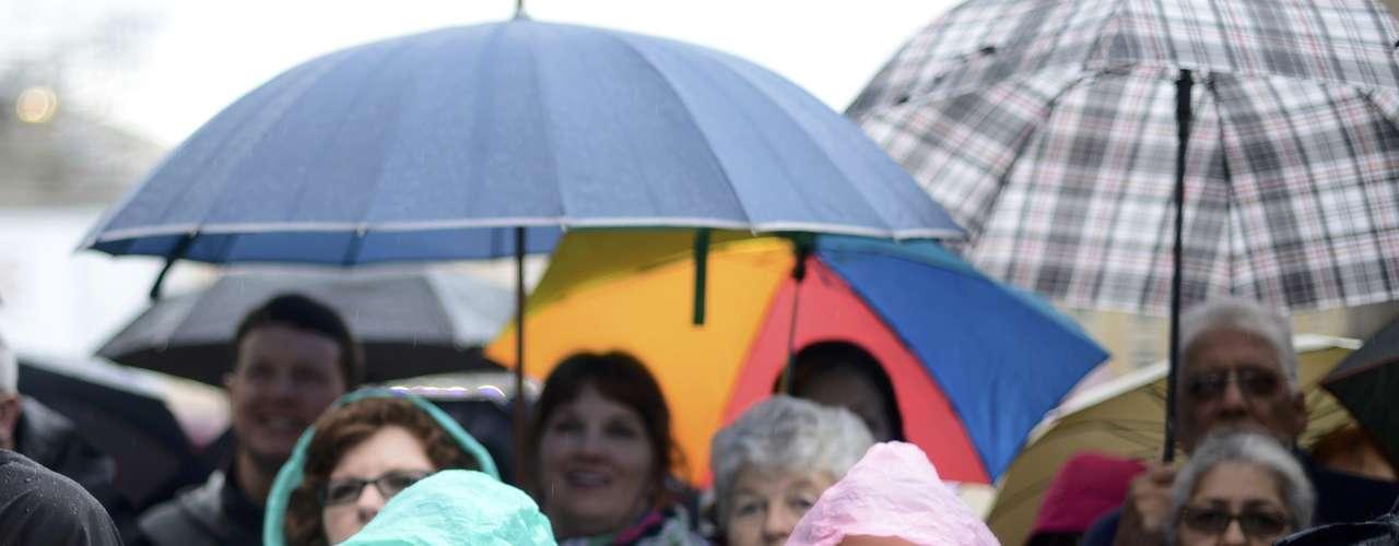 12 de março - Fieis enfrentam a chuva para acompanhar da Praça São Pedro, no Vaticano, a missa que acontece na Capela Sistina