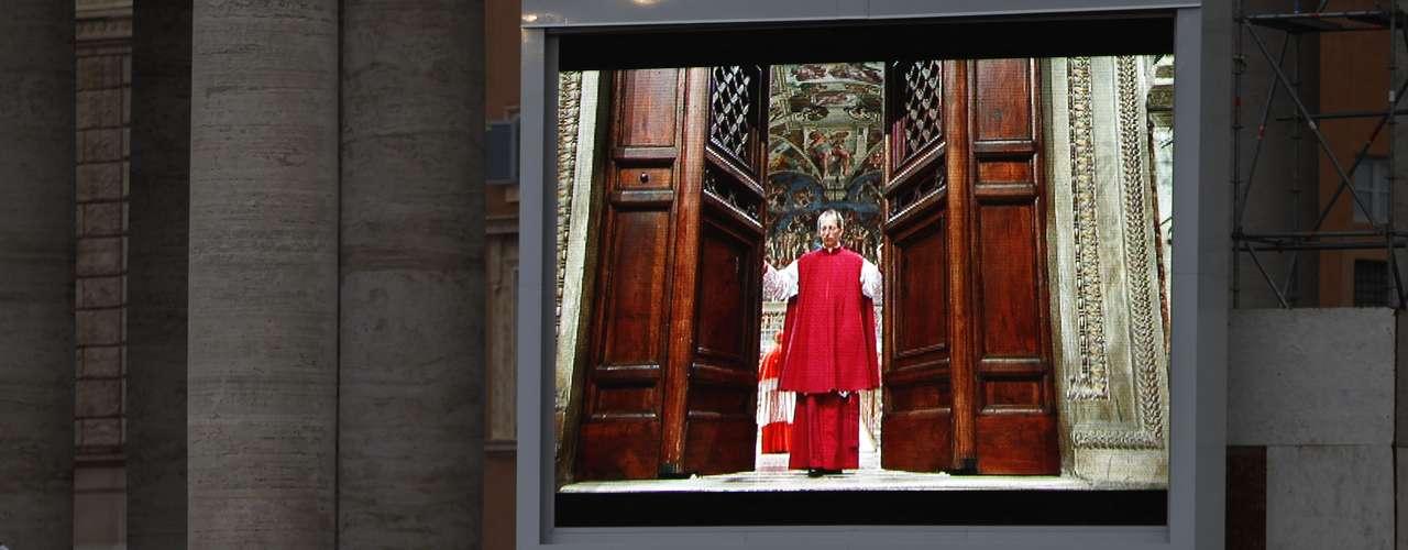 12 de março - Fieis acompanham por um monitor o monsenhor Guido Marini fechando as portas da Capela Sistina para o início do conclave, após o comando em latim \