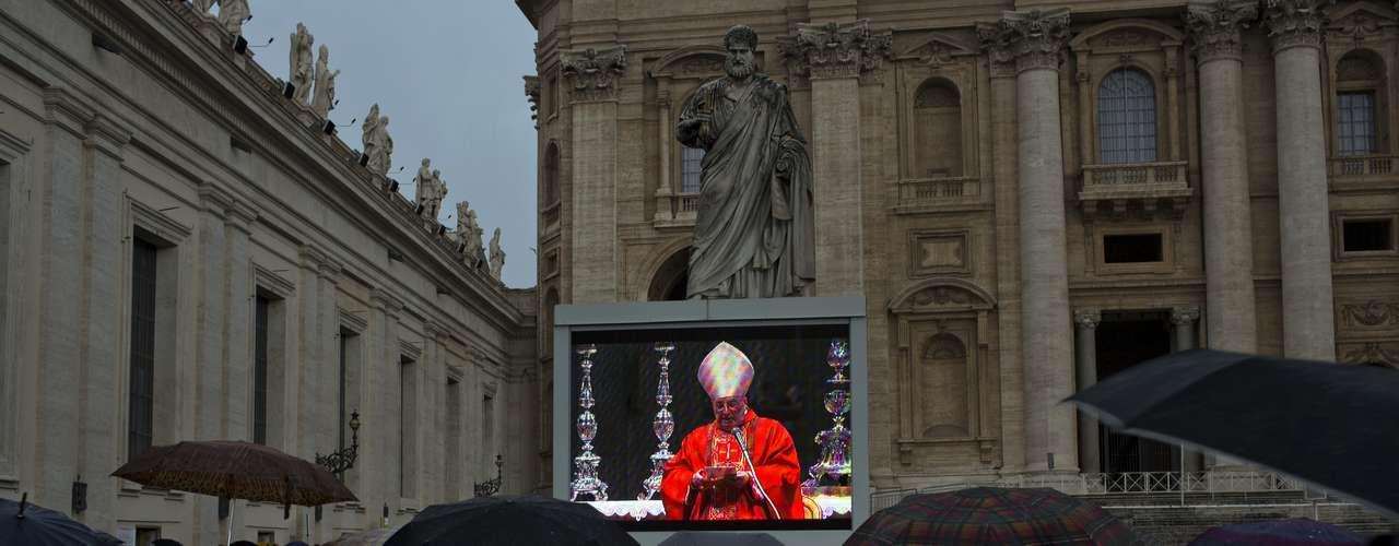 12 de março -Fiéis se protegem da chuva enquanto acompanham transmissão de missa celebrada pelo cardeal Angelo Sodano na Basílica de São Pedro, na Cidade do Vaticano
