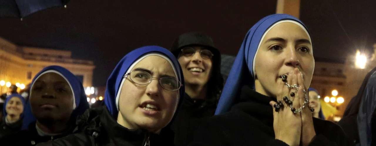12 de março - Fiéis e freiras reagem à fumaça preta que sai da chaminé da Capela Sistina, indicando que Igreja Católica ainda não tem um novo papa
