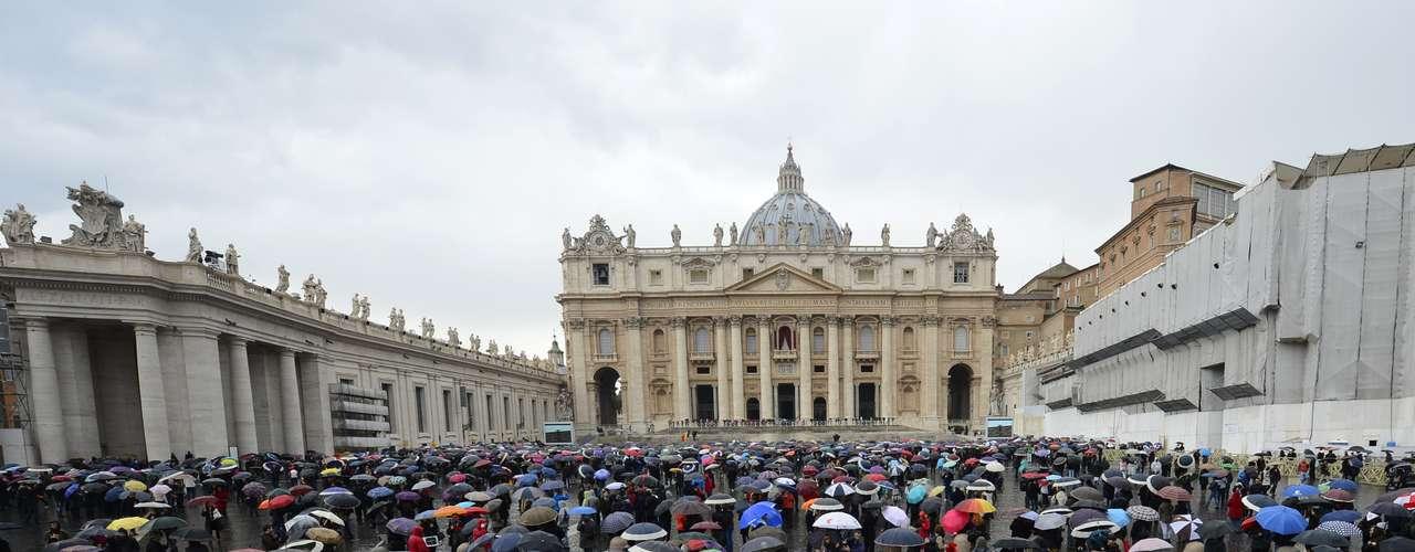 13 de março - Sob guarda-chuvas, para se proteger da precipitação intermitente no Vaticano, devotos aguardam fumaça que anunciará resultado da votação do Conclave