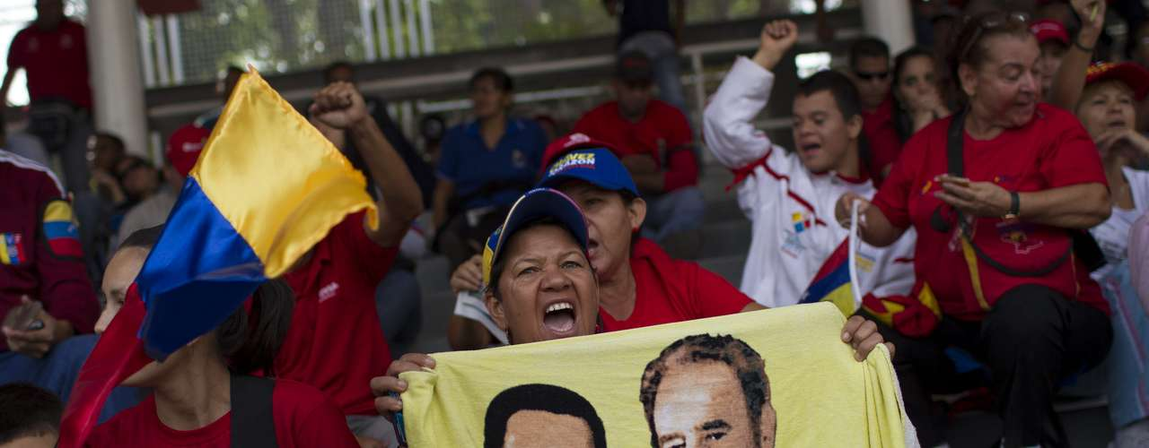 15 de março -Seguidora de Chávez exibe bandeira venezuelana com o rosto dele e do líder cubano Fidel Castro
