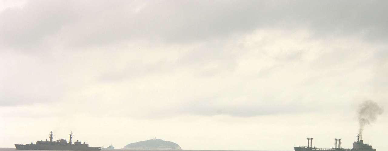 27 de março Banhistas observam navios passando pelo mar de Copacabana, no Rio de Janeiro, durante manhã nublada na capital fluminense