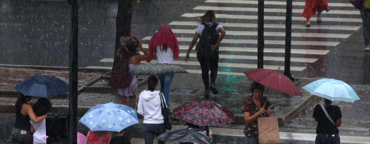 27 de março Pedestres se protegem da chuva em Belo Horizonte, na tarde desta quarta-feira