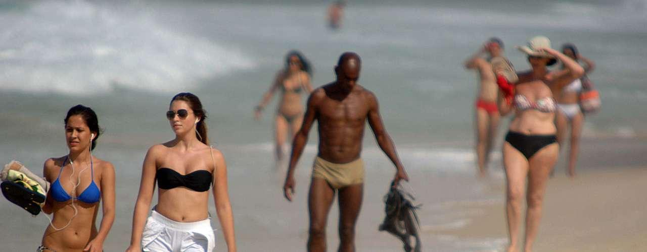 2 de abril Banhistas caminham na beira da praia de Ipanema em um dia de sol