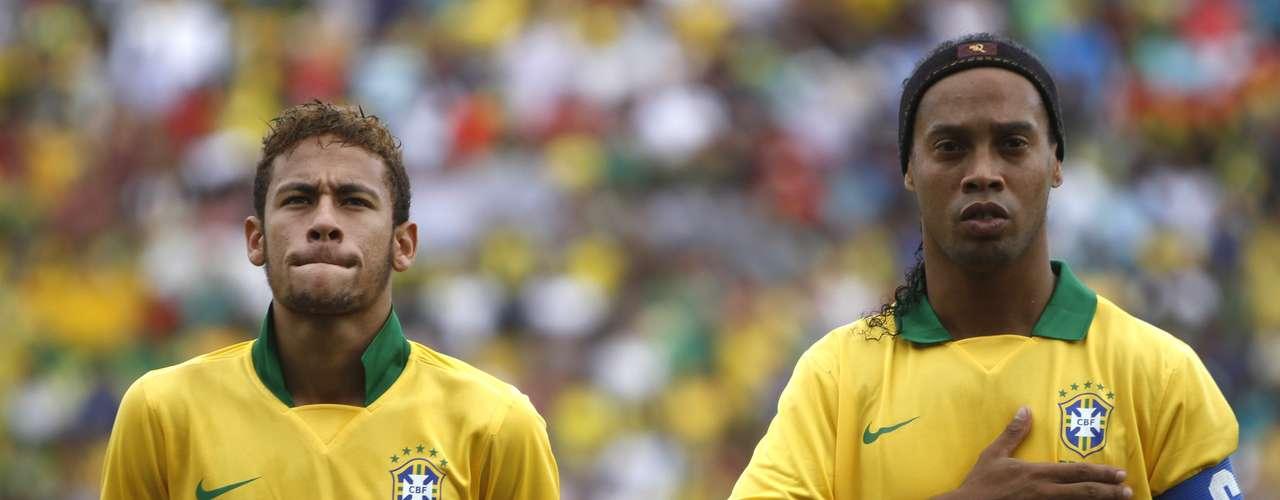 Neymar e Ronaldinho cantam o hino, após apresentarem faixa que pedia paz nos estádios