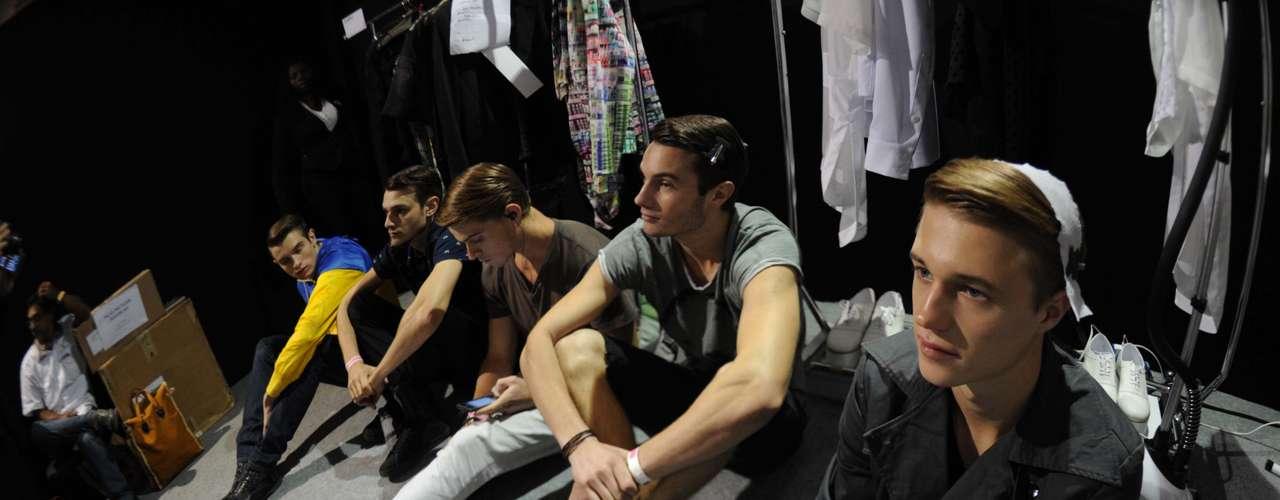 Sentados no chão, modelos aguardam antes de subir à passarela do Fashion Rio