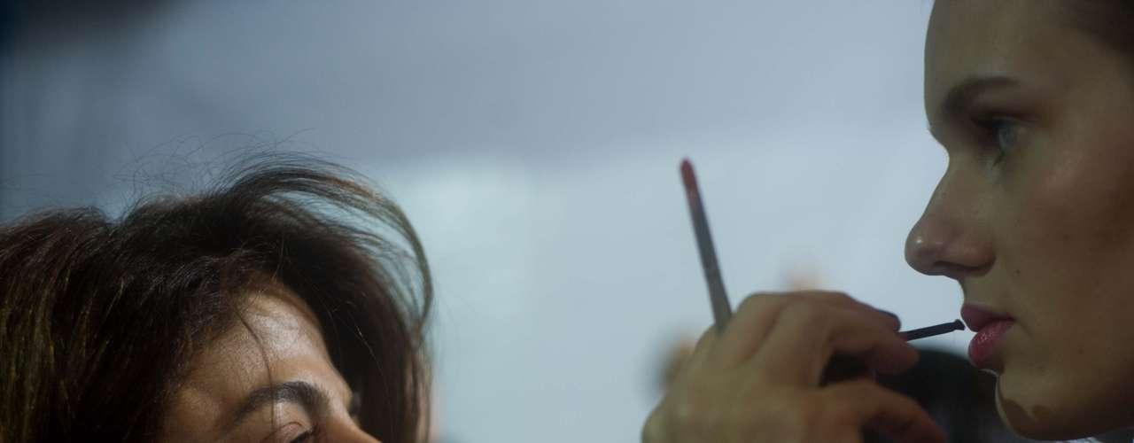 Maquiadora passa batom em modelo
