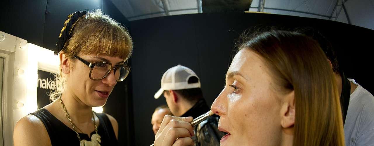 Modelo é maquiada por profissional antes de entrar na passarela pela grife Espaço Fashion