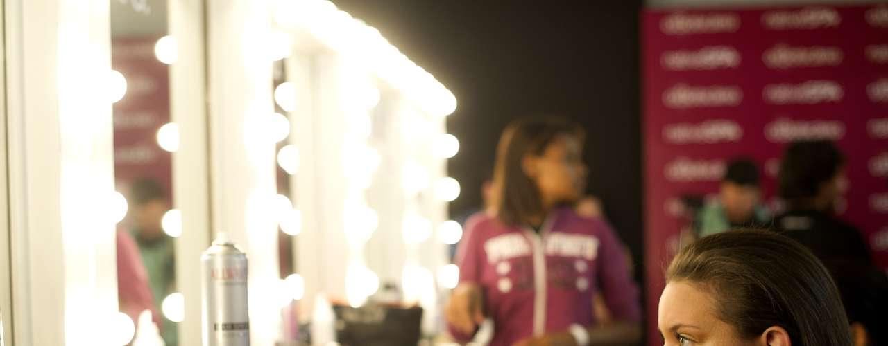 Modelo se olha no espelho antes de entrar na passarela pela grife TNG