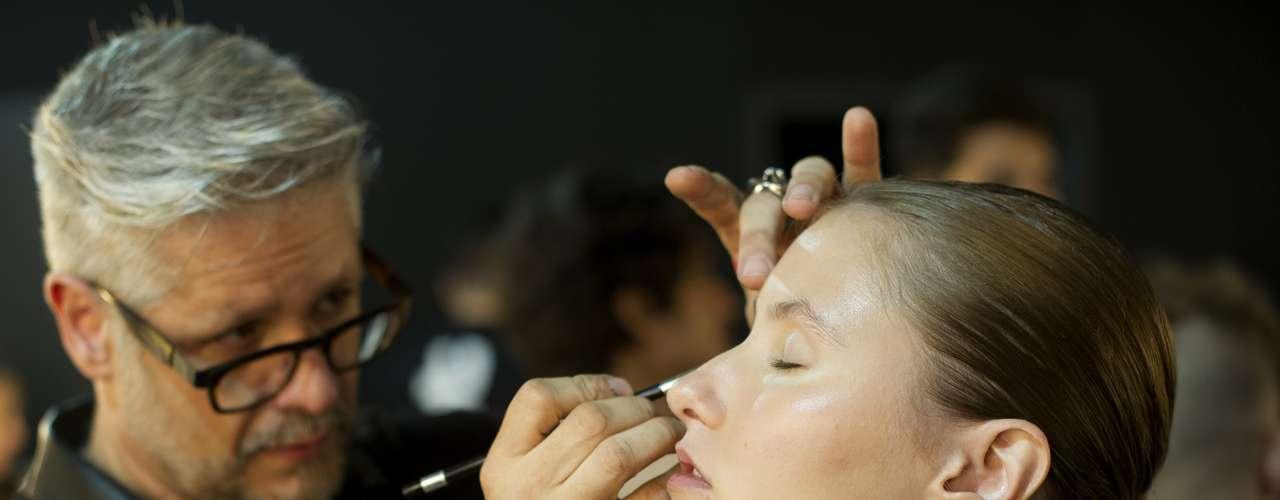 Imagem mostra maquiador passando corretivo no rosto de modelo antes do desfile para a TNG
