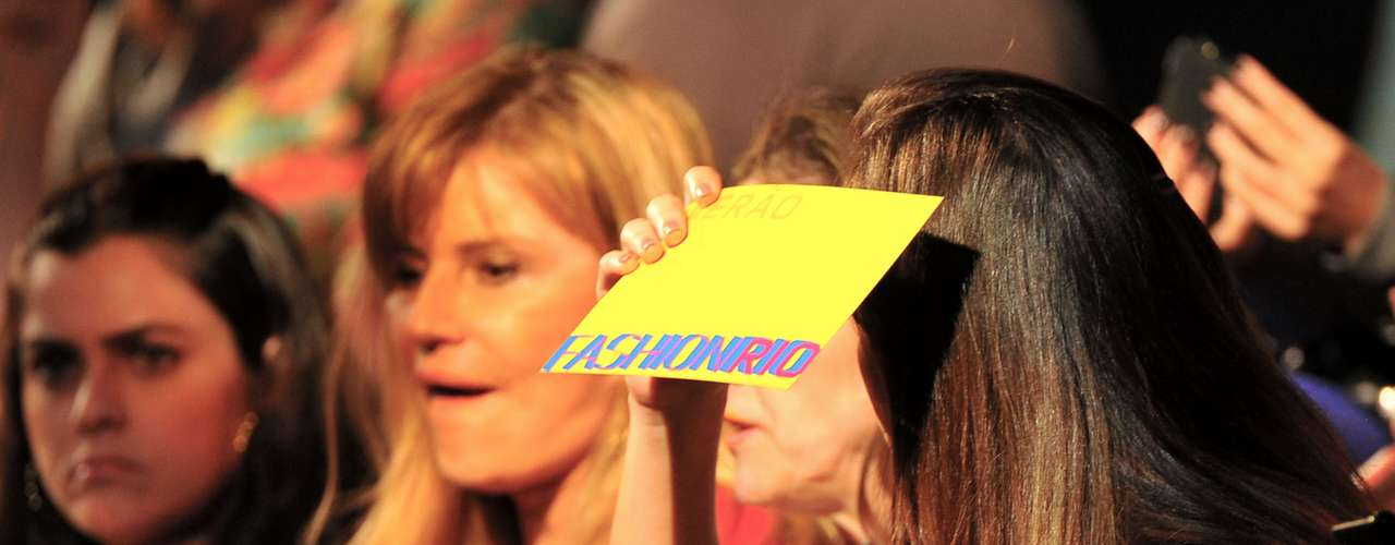 Mulher se protege da luz forte dentro da sala de desfile na Marina da Glória