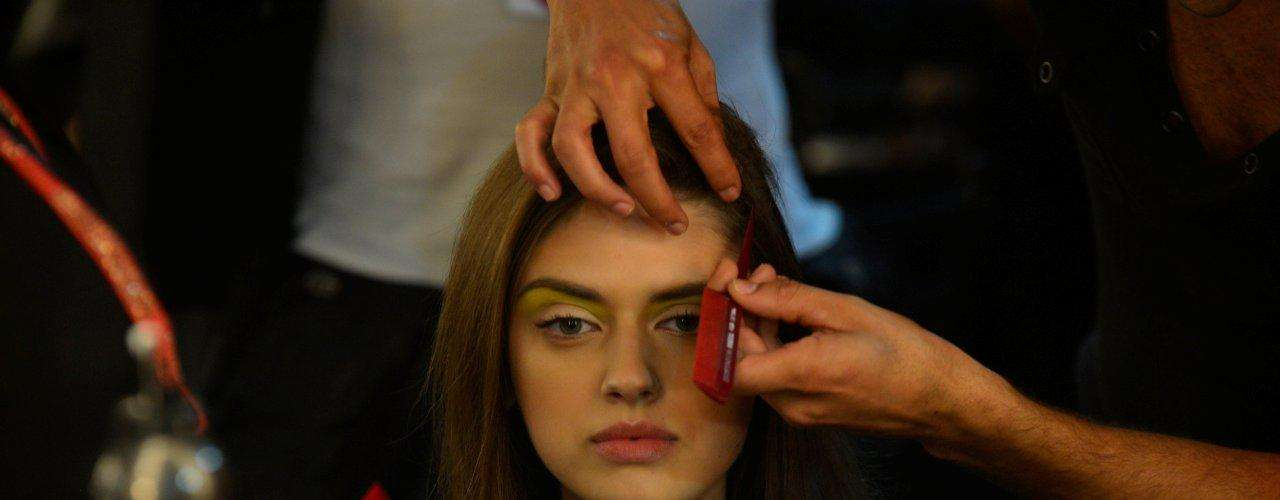 Cabeleireiro utiliza o cabo de um pente fino para desenhar a risca lateral no cabelo da modelo