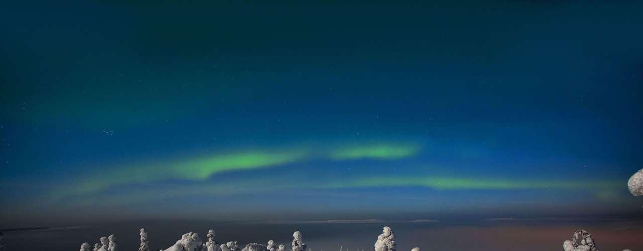 Essa estranha paisagem é composta de árvores cobertas de neve e a aurora boreal. O registro foi feito por Tiina Tormanen, na Finlândia, a uma temperatura de -20°C