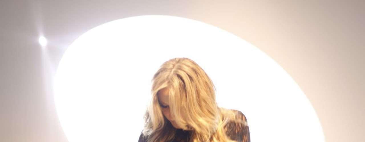 Nas fotos do makingof, a cantora aparece usando um vestido preto com renda