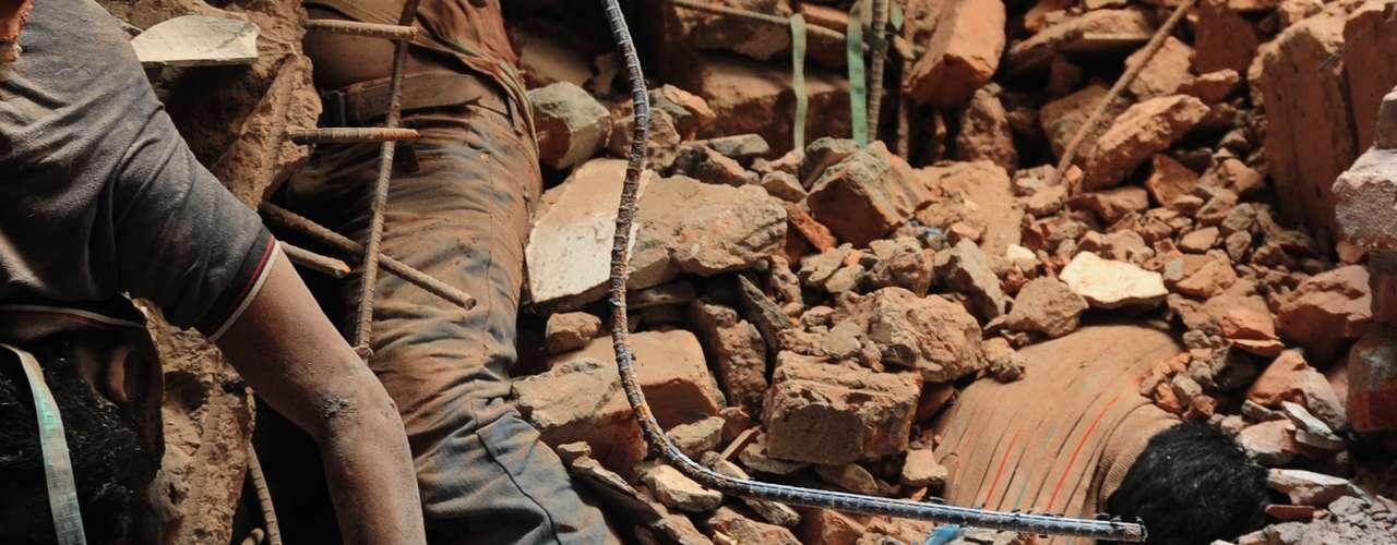 25 de abril -Corpos de trabalhadores mortos são vistos em meio aos destroços