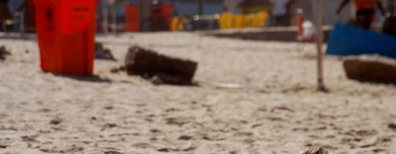 26 de abril Garota toma banho de sol na beira da praia de Ipanema