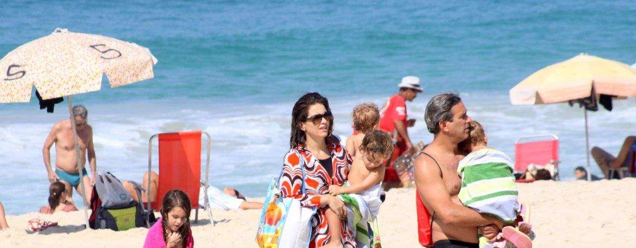 Abril 2013 -Claudia Abreu esteve na praia do Leblon, zona sul do Rio de Janeiro, neste domingo (28). Usando um maiô comportado, a atriz entrou no mar e se divertiu com o marido, José Henrique Fonseca, e com os filhos
