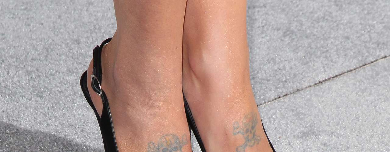 Nos pés da cantora estão duas caveiras