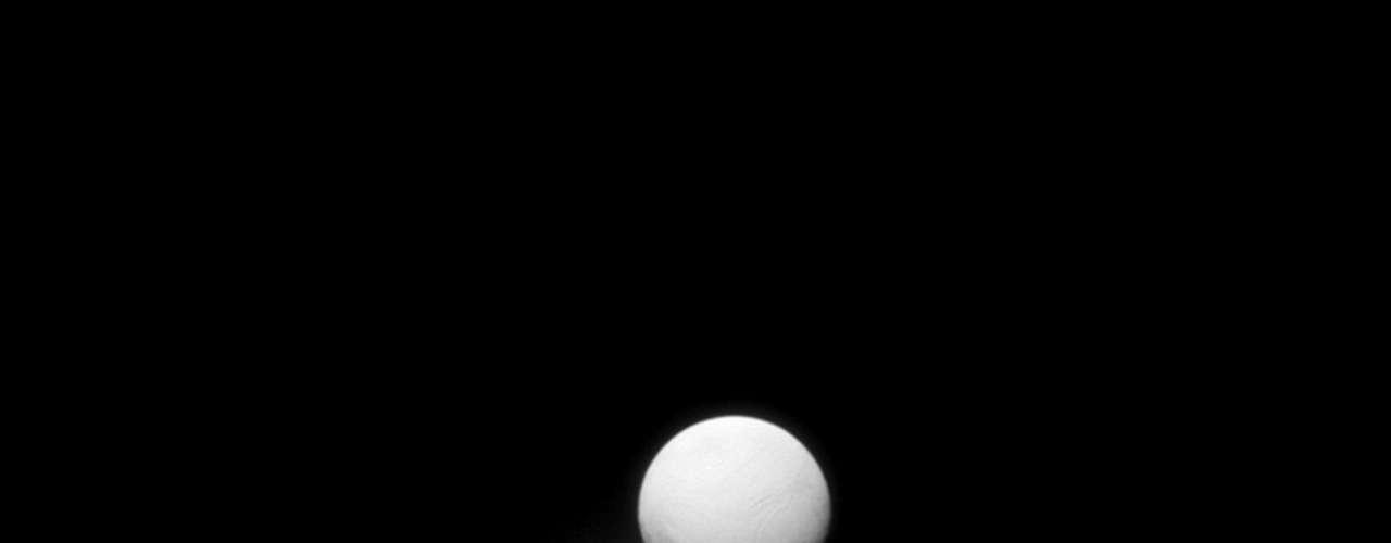 Como um orgulhoso pavão mostrando sua cauda, a lua Encélado, satélite natural de Saturno, foi registrada pelas câmeras da sonda Cassini. Na imagem,Encélado é iluminada pela luz refletida em Saturno