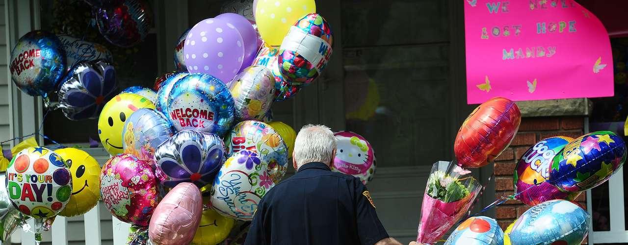 8 de maio - Um policial carrega balões depositados na casa da família de Amanda Berry