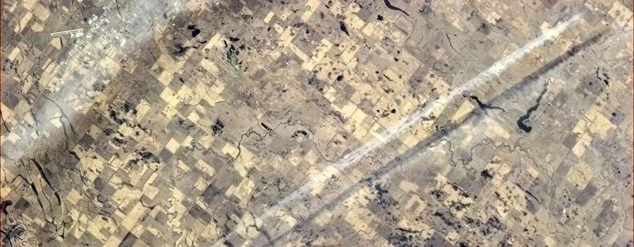 Imagem postada por Chris Hadfield no Twitter nesta segunda-feira, 13 de maio, mostra rastro de um avião na Terra. \