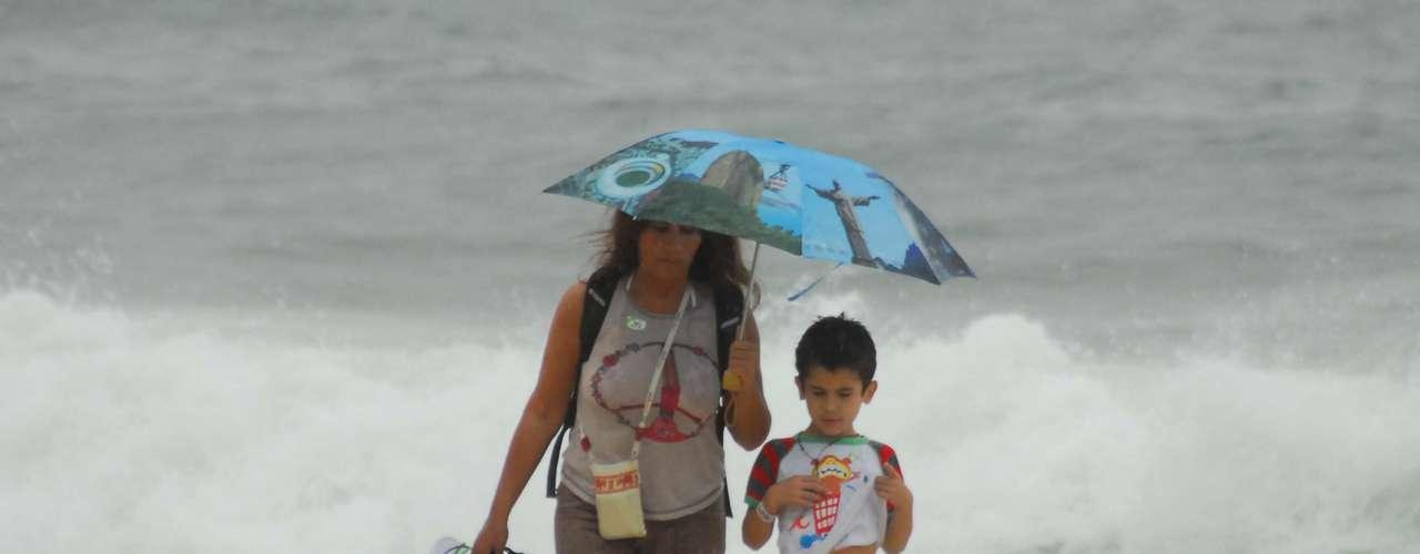 17 de maio Mulher e criança na praia de Copacabana em dia frio e chuvoso