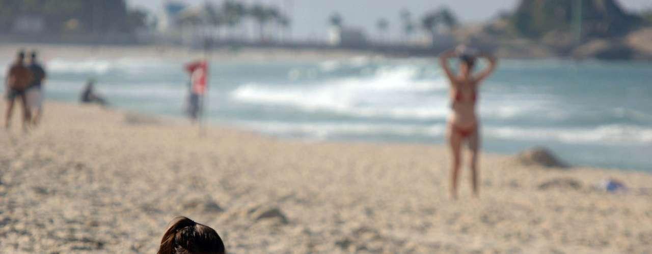 21 de maio - Banhista prefere a leitura na praia carioca de Ipanema