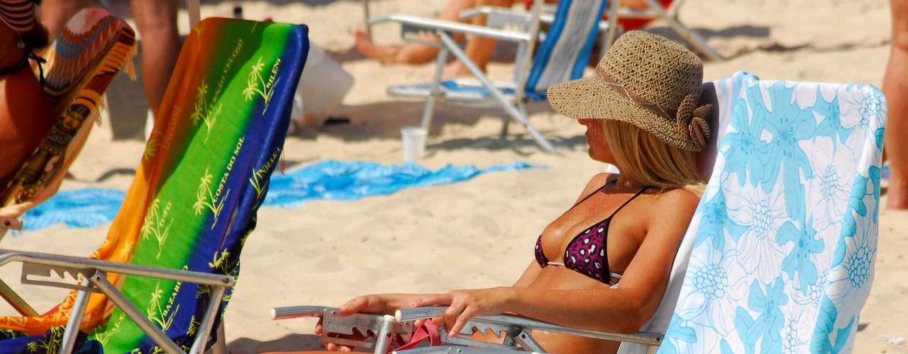 1º de junho Jovem protege o rosto com chapéu ao tomar banho de sol na praia de Copacabana