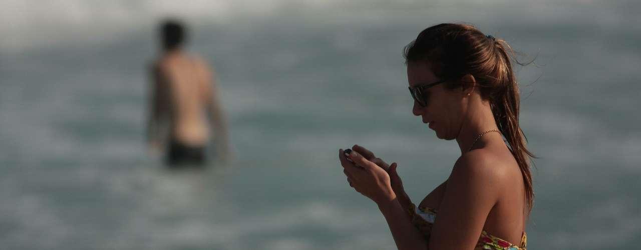 9 de junho -Carioca confere o celular enquanto caminha na praia