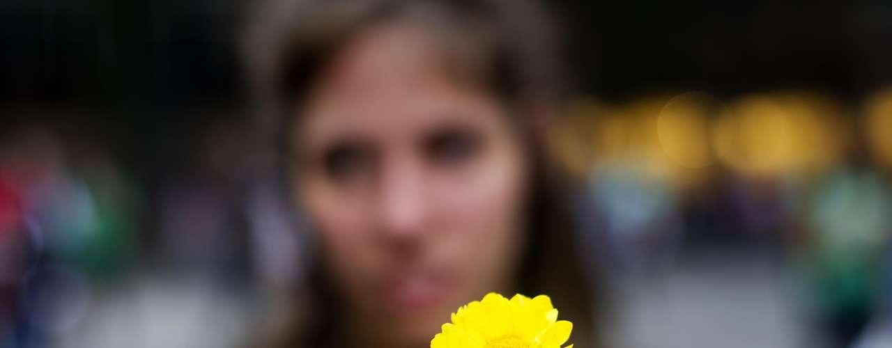 13 de junho - Jovem mostra flor que será distribuída no protesto