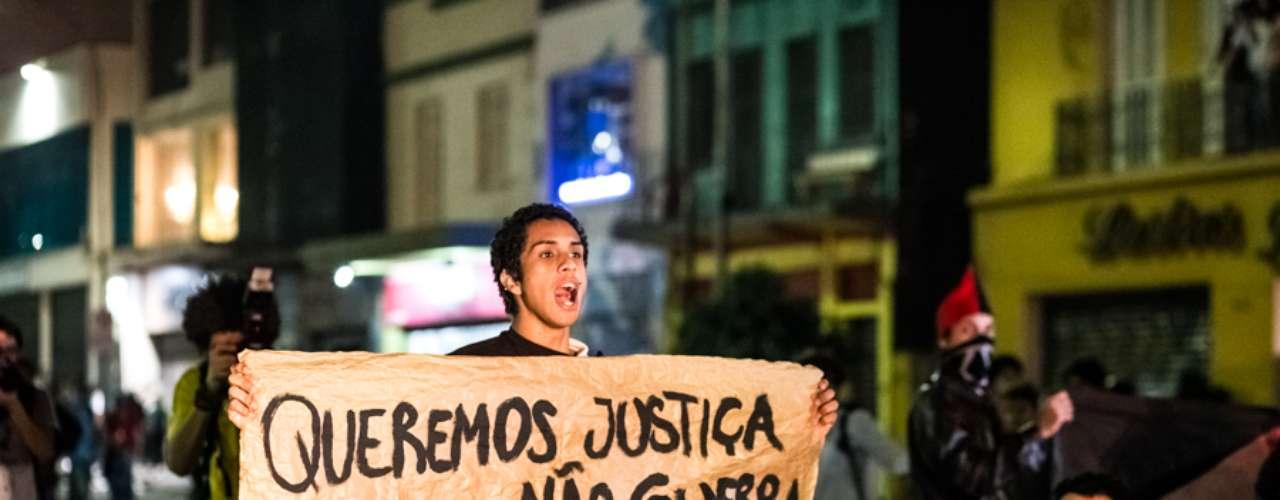 13 de junho -Jovem segura faixa durante manifestação e pede trégua na violência