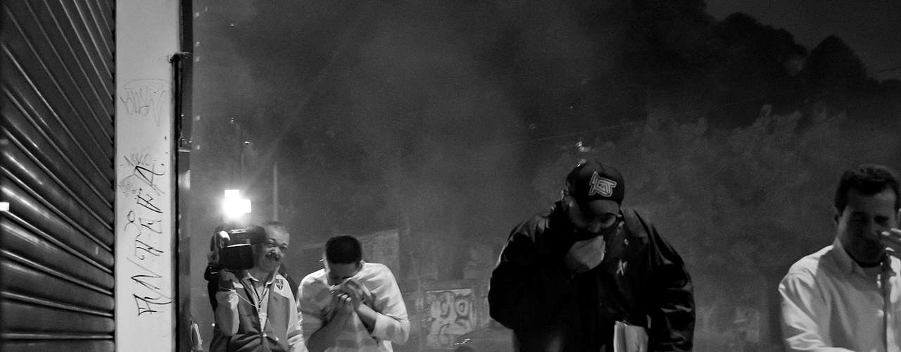 13 de junho - Manifestantes fogem das bombas de gás lacrimogênio atiradas para conter o protesto