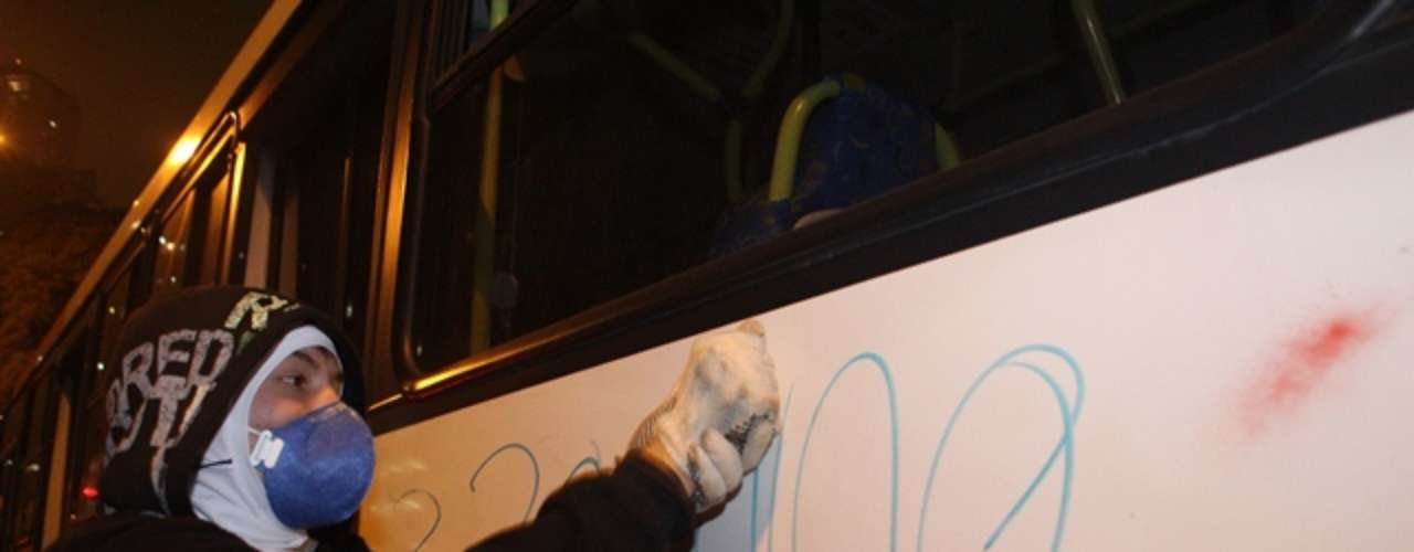13 de junho - Manifestante mascarado picha ônibus durante protesto