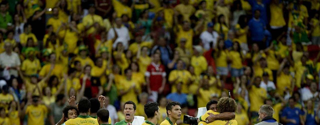 Equipe se abraça, celebrando a vantagem no primeiro jogo da Copa das Confederações